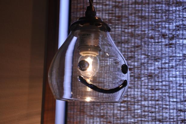 『笑』の手洗い鉢の上にはガラス作家の秋友氏のかわいらしい笑顔の照明