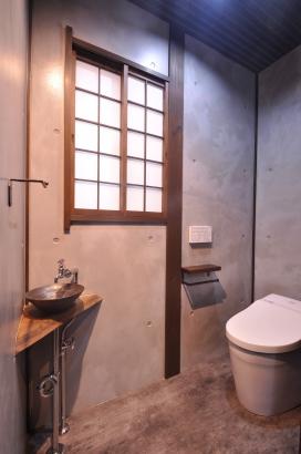 モルタル風塗りの無機質なトイレ。