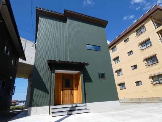 玄関の木質感とスッキリとしたガルバ鋼板の外壁がマッチしています