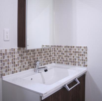 洗面化粧台の扉カラーに合わせた可愛らしいデザインのタイル。