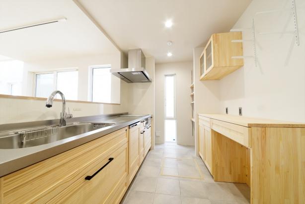 木の温もりを感じるキッチン。キッチン前に少し高めの壁を設けて、手元を隠しています。