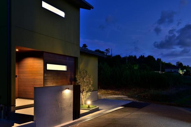 ポーチの杉板張り、シンボルツリーのオリーブ、塗り壁の門袖が良い玄関廻りを演出する