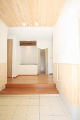 親世帯玄関/旧家屋の欄間と御影石の天板を転用してデザインした飾棚を設けている。