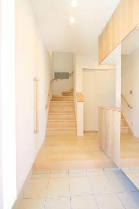 子世帯玄関/階段には照明の点灯で世帯間の気配を感じられる子窓を設けている。
