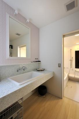 洗面台はタイルによってシンプルに造作された。パウダールームとしても使えるようにカウンターは広く。下部にはキャビネットなどを設けずに、ワゴンやシェルフで仕切れるように。