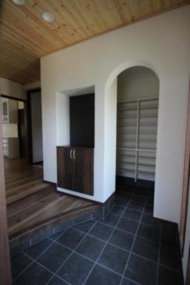 玄関からシューズクローゼットへつながり、大容量の靴が収納できます。壁のRや玄関框のRが優しさをプラスしています。