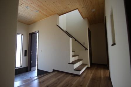 玄関ホール。天井にはパインの羽目板、壁には漆喰の塗壁を使用し、自然素材にあふれた空間でお出迎えです。