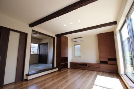 壁面に収納たっぷりのTVボード。和室との間仕切り壁には家具を埋込み、両側から使えるようになっています。