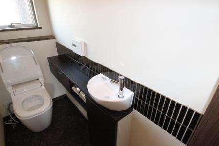 階段下を利用したトイレ。手洗い部分には水が飛び散るのでタイルを使用しデザインもプラス。