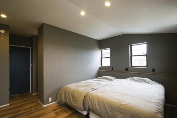 壁の色は濃いグレーで落ち着いた色合いの寝室。