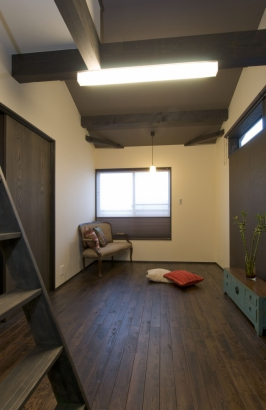 太い梁を現した主寝室。はしごを登って畳のロフトに上がる。