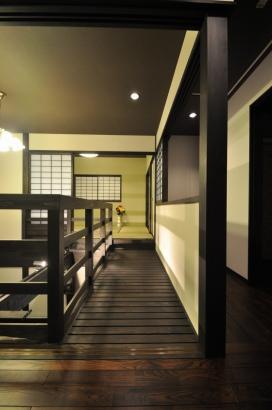 吹き抜けを中心に階段とキャットウォークが囲炉裏の間の上空を一周する。その周りに和室や寝室など配置。