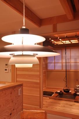 アメリカ製の薪ストーブ、北欧の名作デザイン照明、囲炉裏の間…。個民家基らしい自由なスタイルだ。