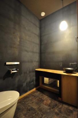 黒壁に白木の造作カウンターがアクセントになっているトイレ