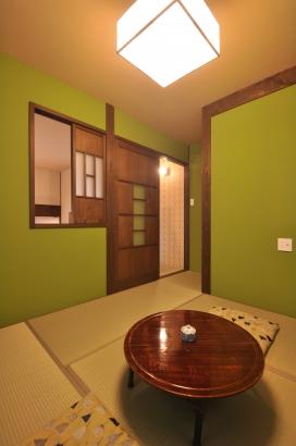 落ち着いた抹茶色の塗り壁の寝室