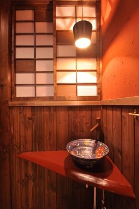 朱壁の厠。カウンターは漆塗り。紺色の手洗い鉢が朱壁のポイントとなり粋な感じ