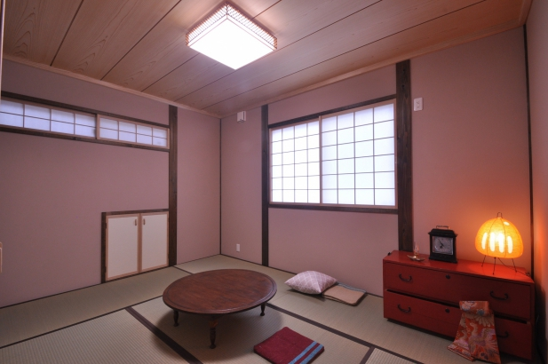 白木色と茶色の塗装、桜色の塗り壁が温かみのある寝室