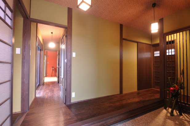 鶯色の落ち着いた塗り壁の玄関。