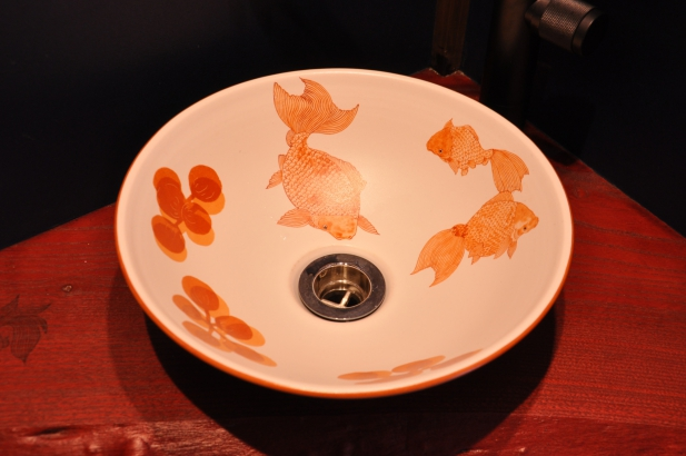 手洗い鉢には九谷庄三の金魚を描き、漆塗りのカウンターにも金魚が鉢から跳ねたイメージで描きました。