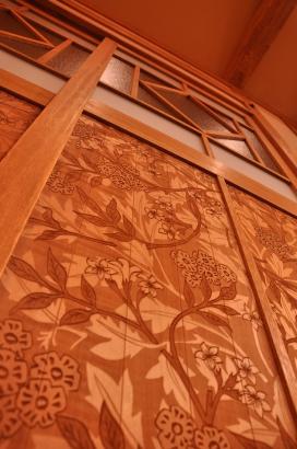 リビングの一部に使われた花柄の壁紙をモチーフにレーザー加工した建具の羽目板。