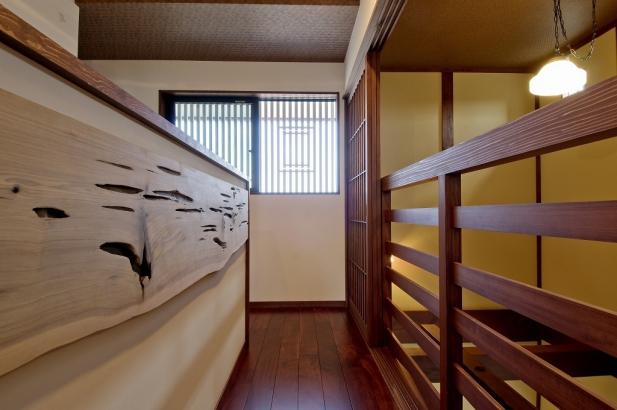 扉を開けると囲炉裏の間を見下ろせます。腰壁には神大杉をアクセントに。