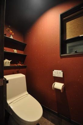 店舗のトイレはインパクトのある朱色の和紙の壁紙