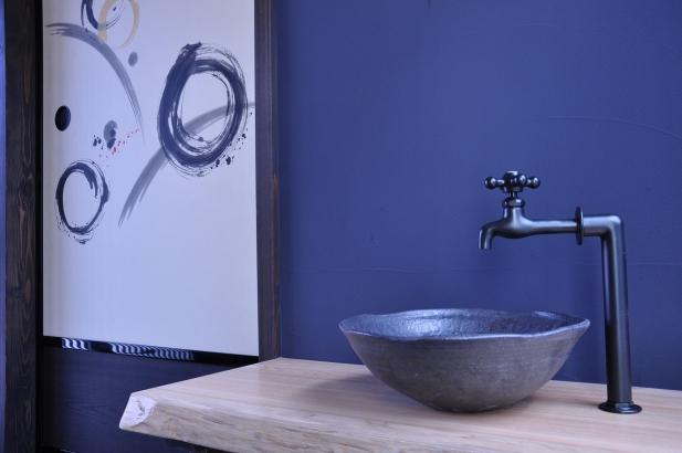 紺壁の玄関土間と渋い色の手洗い鉢