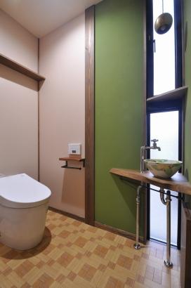 グリーンの塗り壁を差し色にしたかわいらしい雰囲気のトイレ