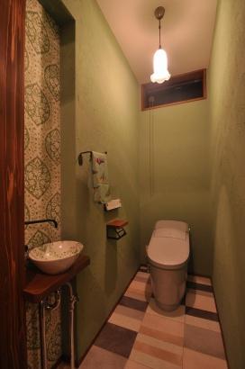 グリーンの塗り壁のトイレにはレトロなデザインの壁紙と手洗い鉢が可愛らしいです。