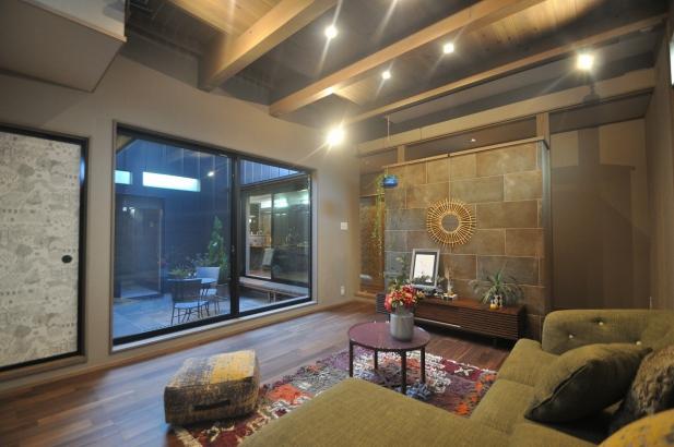 テレビの壁面にはアクセントタイル、天井を見上げると板張りの落ち着いたリビング