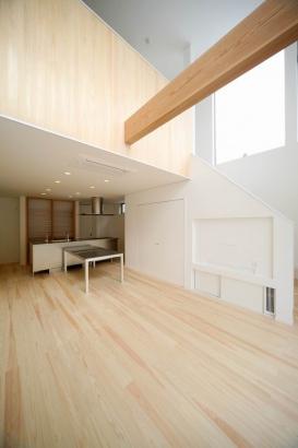 白い空間に無垢材の色。吹き抜けの壁は床材と同じ無垢板貼りです。