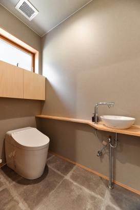 ライトグレーと無垢材の組み合わせのトイレ