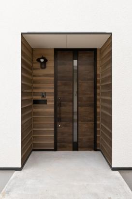 玄関廻りは、板張りに。アンティークな照明ともよく合います。