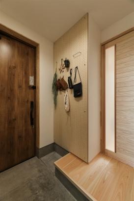 玄関の壁面には、有孔ボードを。普段よく使うものや趣味のものを飾れる壁面。